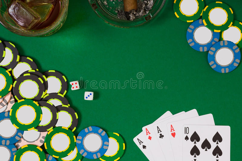 Gambling, fortune and entertainment concept - close up of casino chips, whisky glass, playing cards and cigar on green. Table surface. Top view. Still life royalty free stock image