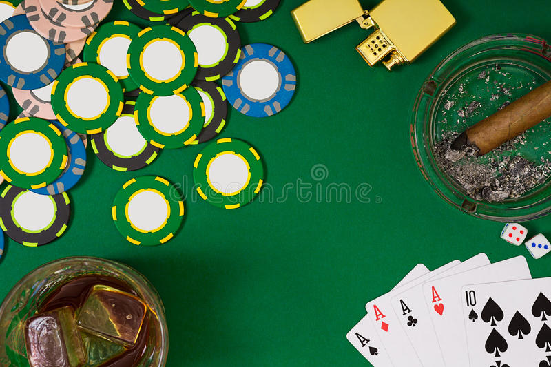 Gambling, fortune and entertainment concept - close up of casino chips, whisky glass, playing cards and cigar on green. Table surface. Top view. Still life royalty free stock images