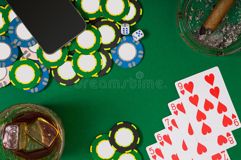 Gambling, fortune and entertainment concept - close up of casino chips, whisky glass, playing cards and cigar on green. Table surface. Top view. Still life stock photography