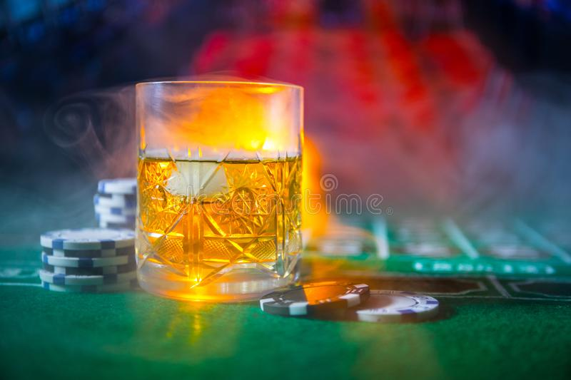 gambling, fortune, game and entertainment concept - close up of casino chips and whisky glass on table stock images