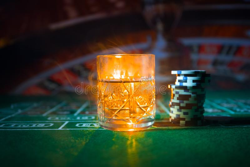gambling, fortune, game and entertainment concept - close up of casino chips and whisky glass on table royalty free stock photography