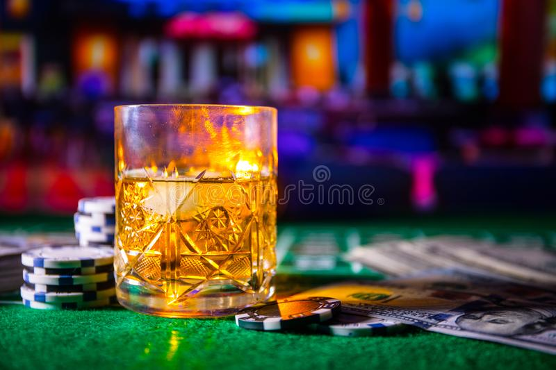 gambling, fortune, game and entertainment concept - close up of casino chips and whisky glass on table stock image