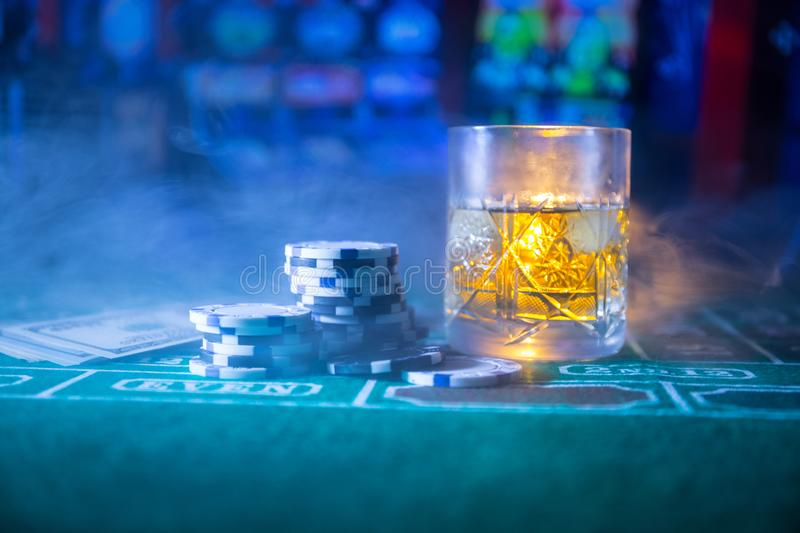 gambling, fortune, game and entertainment concept - close up of casino chips and whisky glass on table stock photography