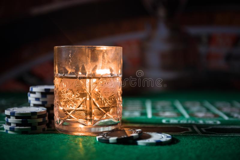 gambling, fortune, game and entertainment concept - close up of casino chips and whisky glass on table royalty free stock photo
