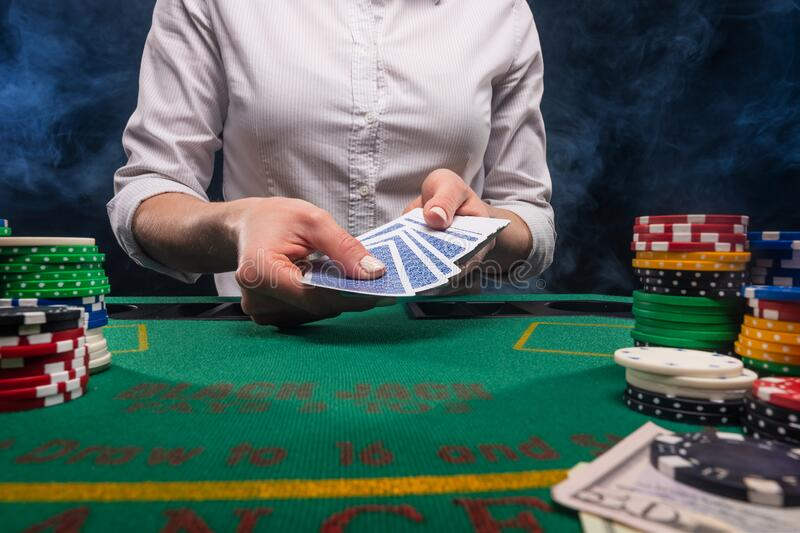 Gambling and gaming business in a casino. Girl hands out cards. Concept of playing cards royalty free stock photography