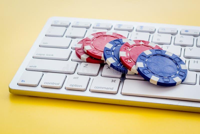 Gambling, online games Chips dichtbij toetsenbord op gele achtergrond stock foto