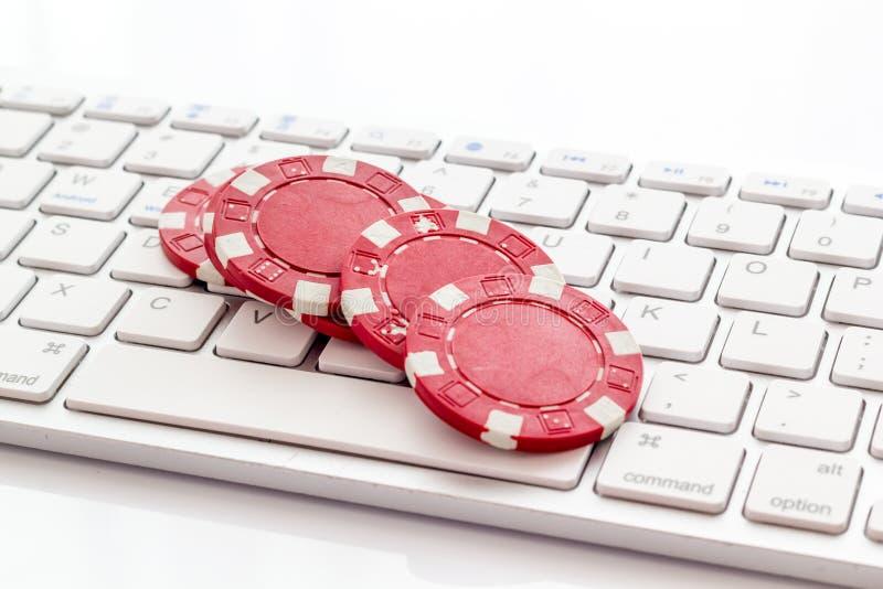 Gambling, online games Chips dichtbij toetsenbord op witte achtergrond stock foto