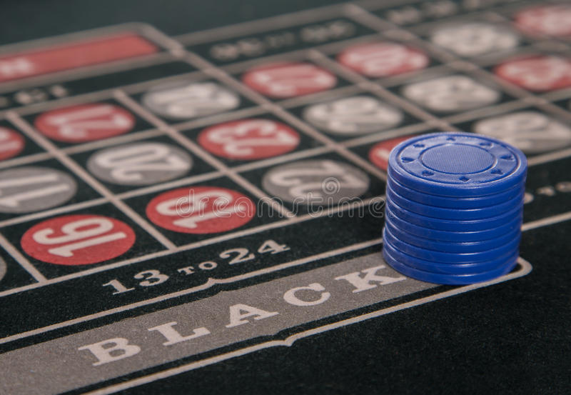 Gambling on a roulette table with blue chips stock photos