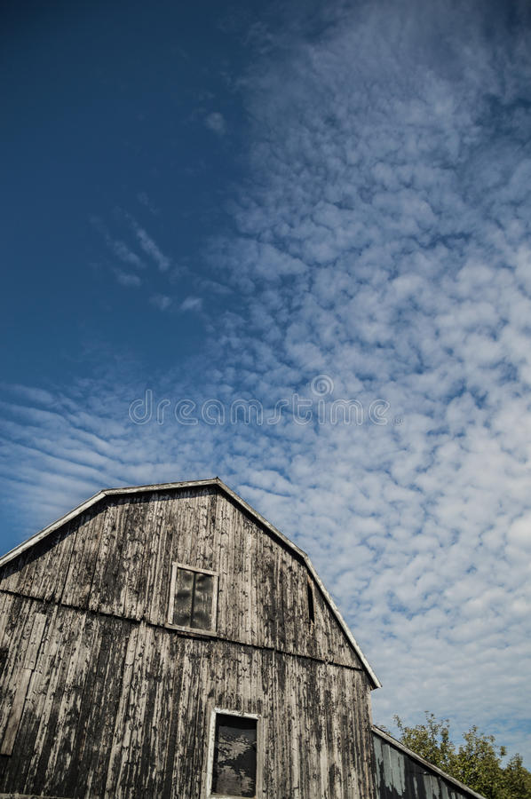 Gambrel roof black weathered barn with deep blue sky and cloudscapes stock photography