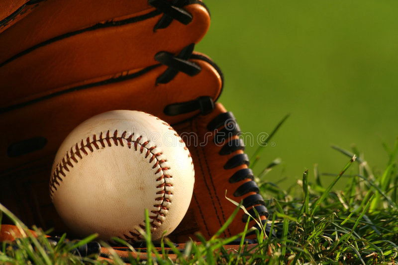 After the game. Baseball and glove on the grass royalty free stock images