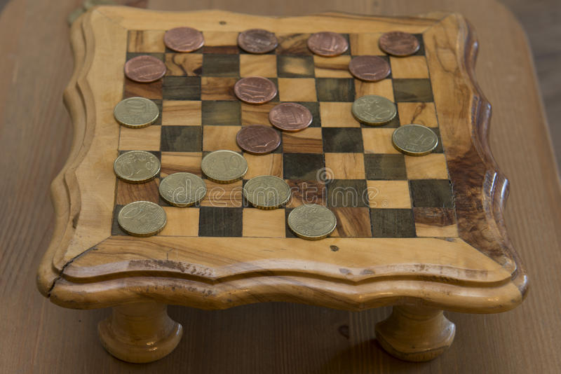 Game of checkers - US cents VS eurocents. Game of checkers - US cents VS euro cents royalty free stock images