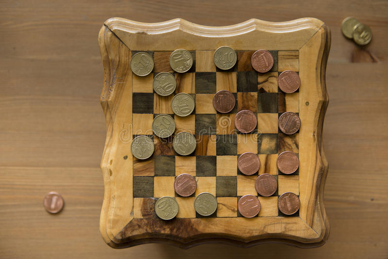 Game of checkers - US cents VS eurocents. Game of checkers - US cents VS euro cents stock photos
