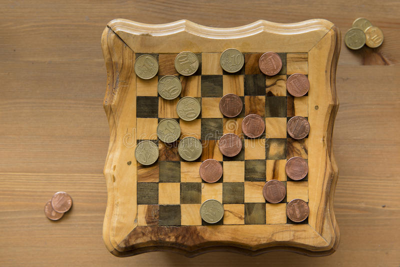 Game of checkers - US cents VS eurocents. Game of checkers - US cents VS euro cents stock photo