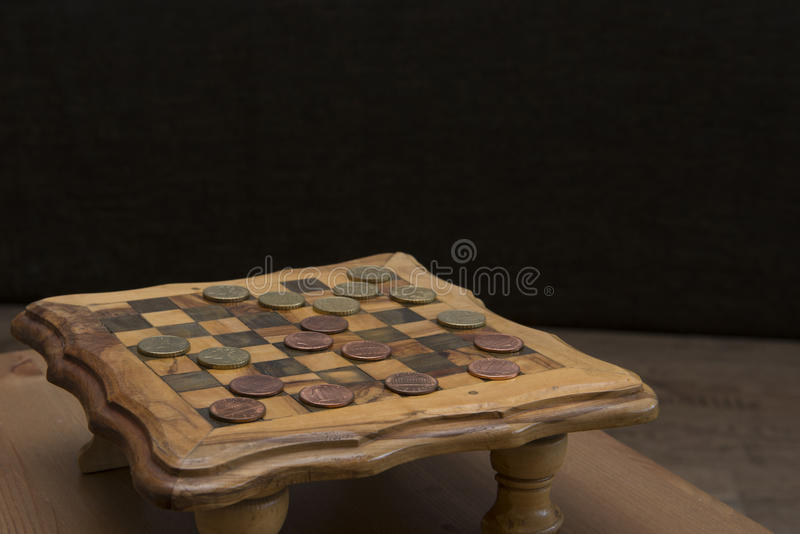 Game of checkers - US cents VS eurocents. Game of checkers - US cents VS euro cents royalty free stock photos