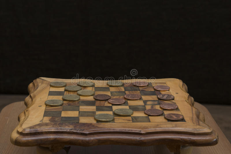 Game of checkers - US cents VS eurocents. Game of checkers - US cents VS euro cents stock images