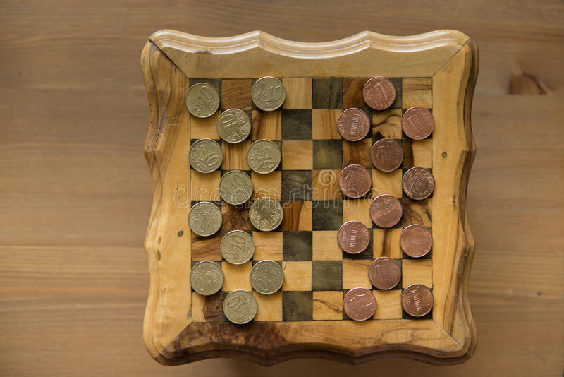 Game of checkers - US cents VS eurocents. Game of checkers - US cents VS euro cents stock photography