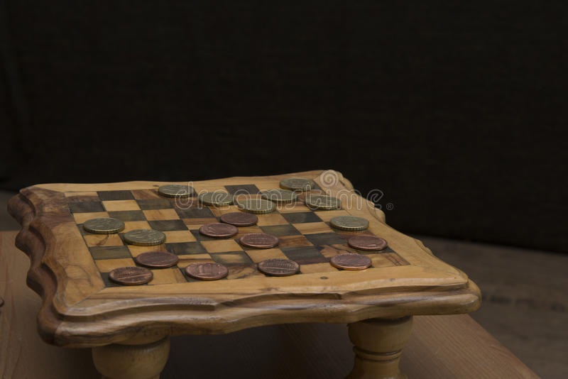 Game of checkers - US cents VS eurocents. Game of checkers - US cents VS euro cents royalty free stock image