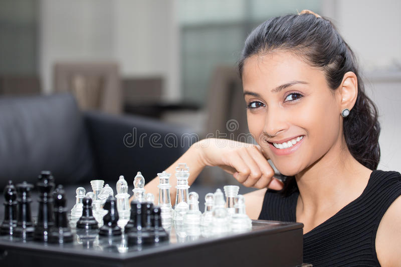 Game of chess. Closeup portrait, thinking woman in black shirt playing chess, wondering next move, isolated indoors background royalty free stock image