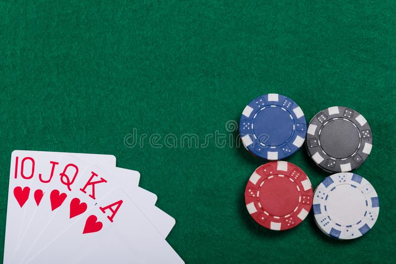 Game chips and cards on the green poker table. A winning combination in Royal Flush poker stock images
