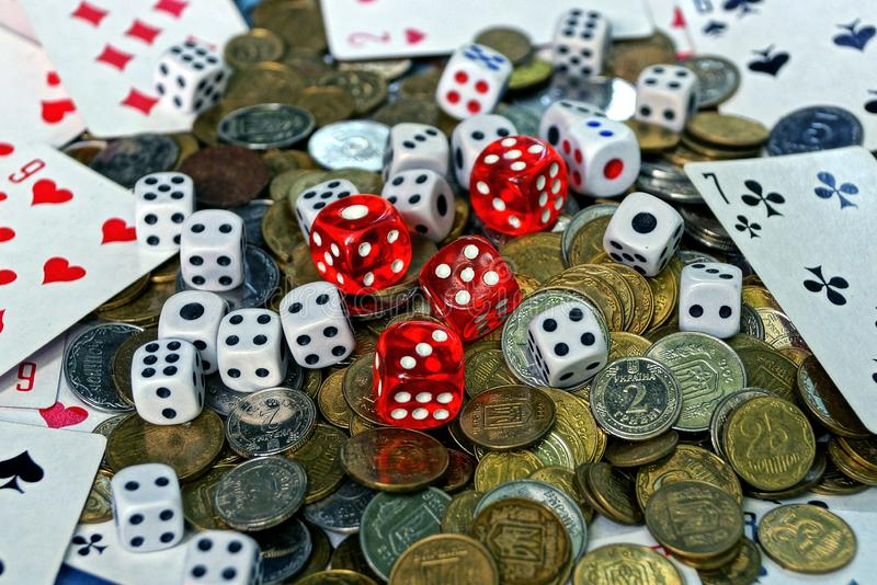 Game dice with game cards in a pile with small coins royalty free stock photos