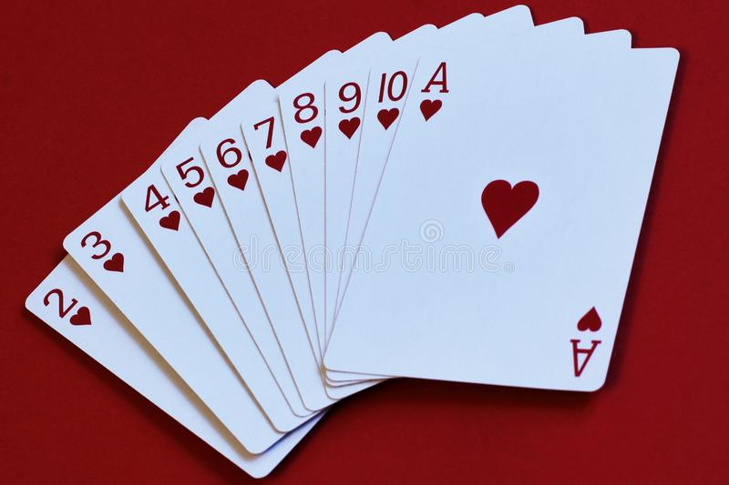 Allegorical way from simple to complex. Fan of cards of heart suit on red background as step by step instruction to achieve goal. Game of imagination. Cards of royalty free stock photography
