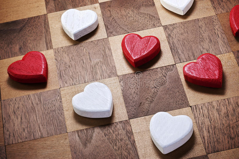 Game Love Heart Checkers. A game of checkers on a checkerboard with love heart shapes for checkers portraying love as a game royalty free stock photo
