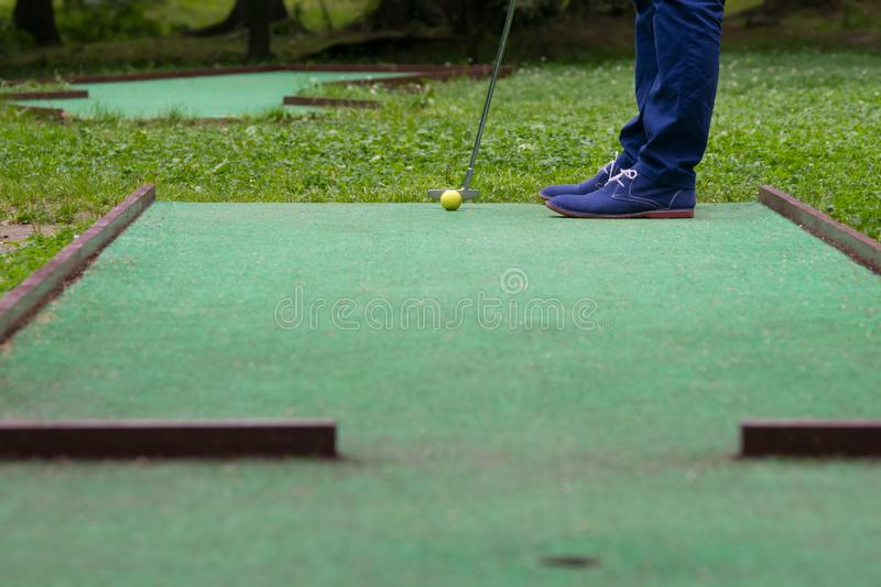 a game of mini-golf, a view from the hole at the time of striking a yellow ball with a stick royalty free stock photography