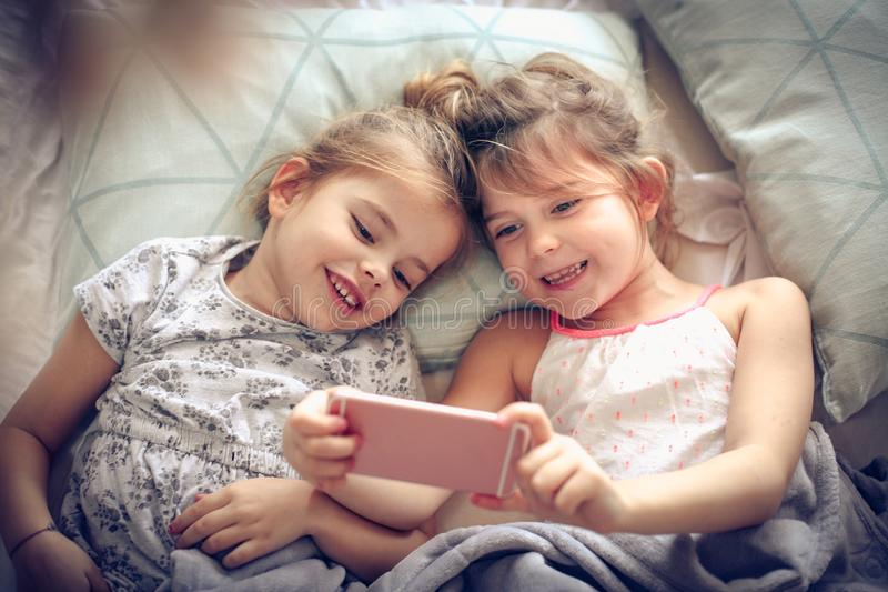 Game on phone. Two little girl using smart phone together stock images