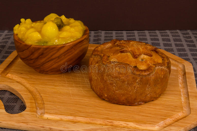Game pie served with bowl of piccalilli. Piccalilli relish in a wooden bowl on a board stock images