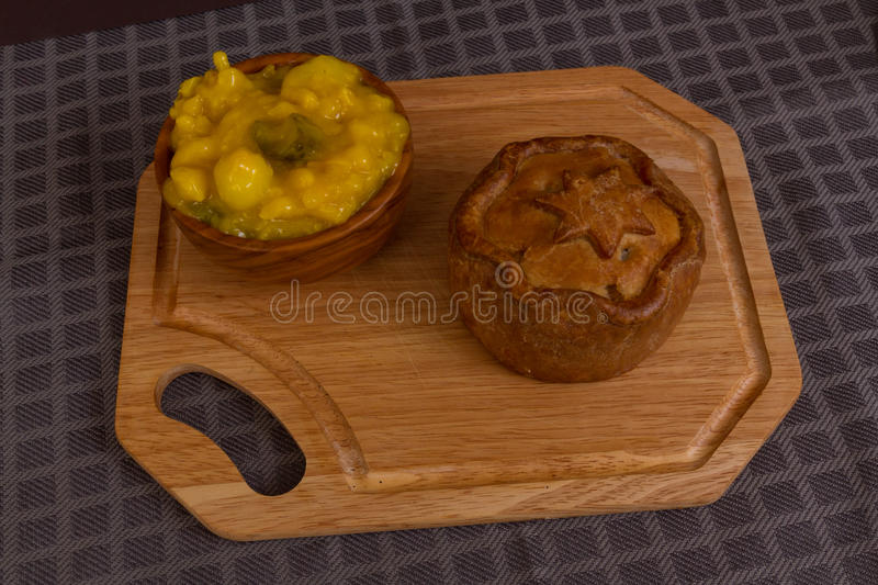 Game pie served with bowl of piccalilli. Piccalilli relish in a wooden bowl on a board stock image