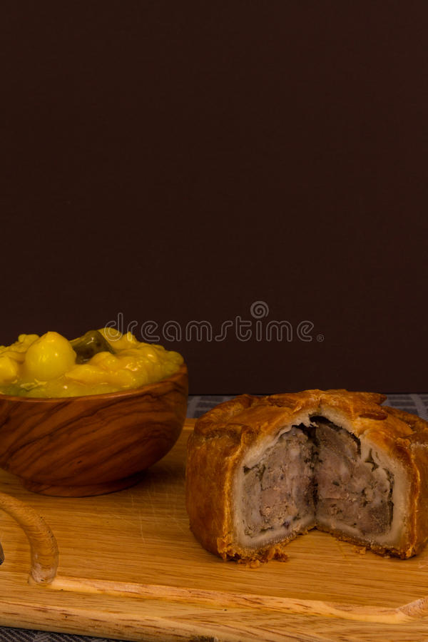 Game pie served with bowl of piccalilli. Piccalilli relish in a wooden bowl on a board royalty free stock photos