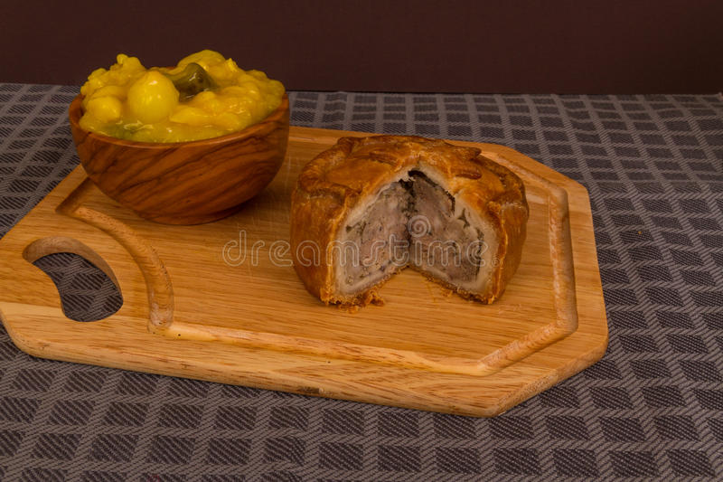 Game pie served with bowl of piccalilli. Piccalilli relish in a wooden bowl on a board royalty free stock image