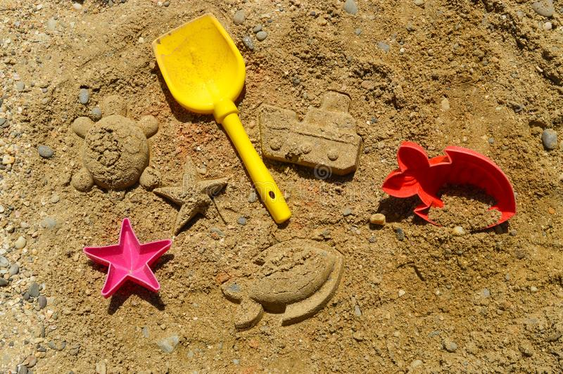 Game in the sandbox on the beach, under the scorching rays of the sun. From accessories - a shovel, molds for sand - fish, a star, and ready figures - a ship stock photo