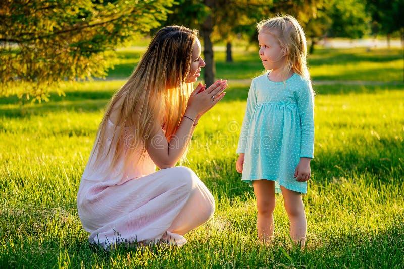 Game of tag schattig blonde meisje in een blauwe jurk met mooie moeder met lange haren die plezier heeft en inhaalslag heeft gema stock foto