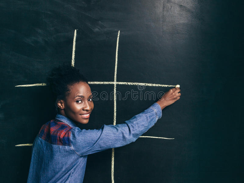Game tic tac toe, afroamerican girl happy to play stock images