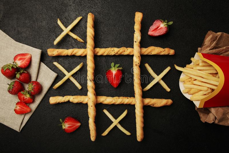 Game of tic tac toe of french fries and strawberry. Choosing healthy vs unhealthy foods. Fit or fat concept stock photography