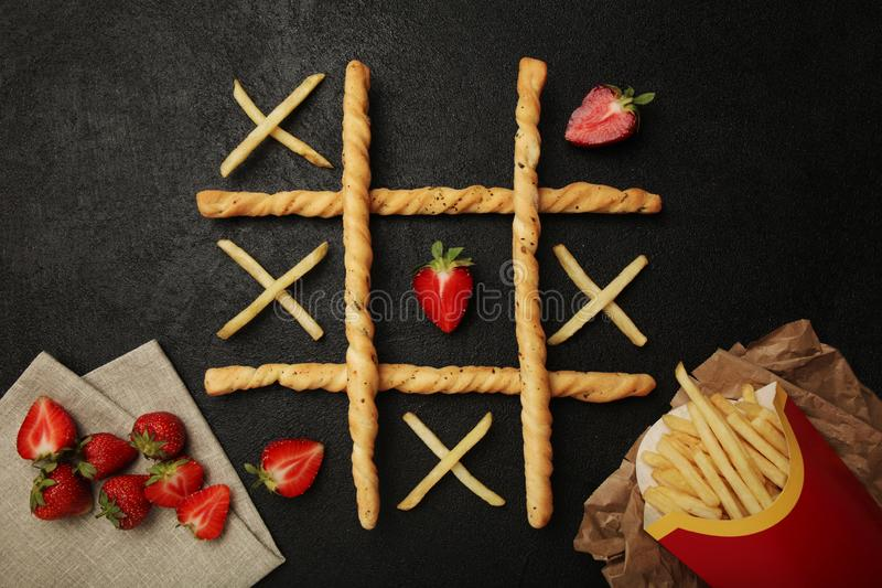 Game of tic tac toe of french fries and strawberry. Choosing healthy vs unhealthy foods. Fit or fat concept.  stock photo