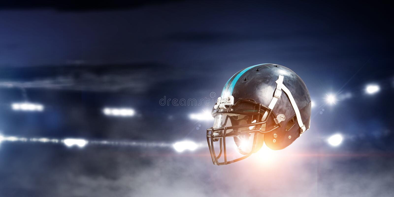 It is game time. Mixed media. American football helmet against rugby stadium. Mixed media stock photos