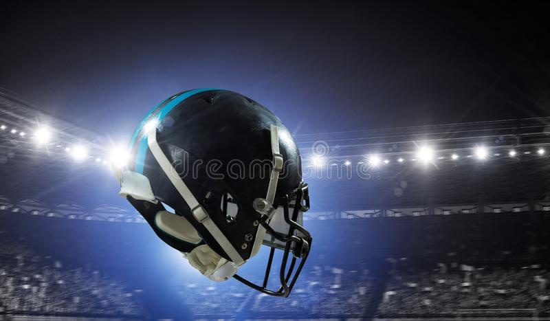 It is game time. Mixed media. American football helmet against rugby stadium. Mixed media royalty free stock photo