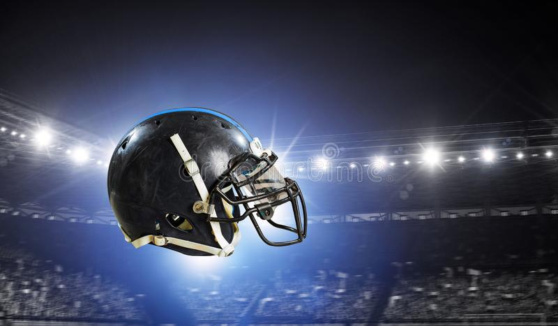 It is game time. Mixed media. American football helmet against rugby stadium. Mixed media stock photography