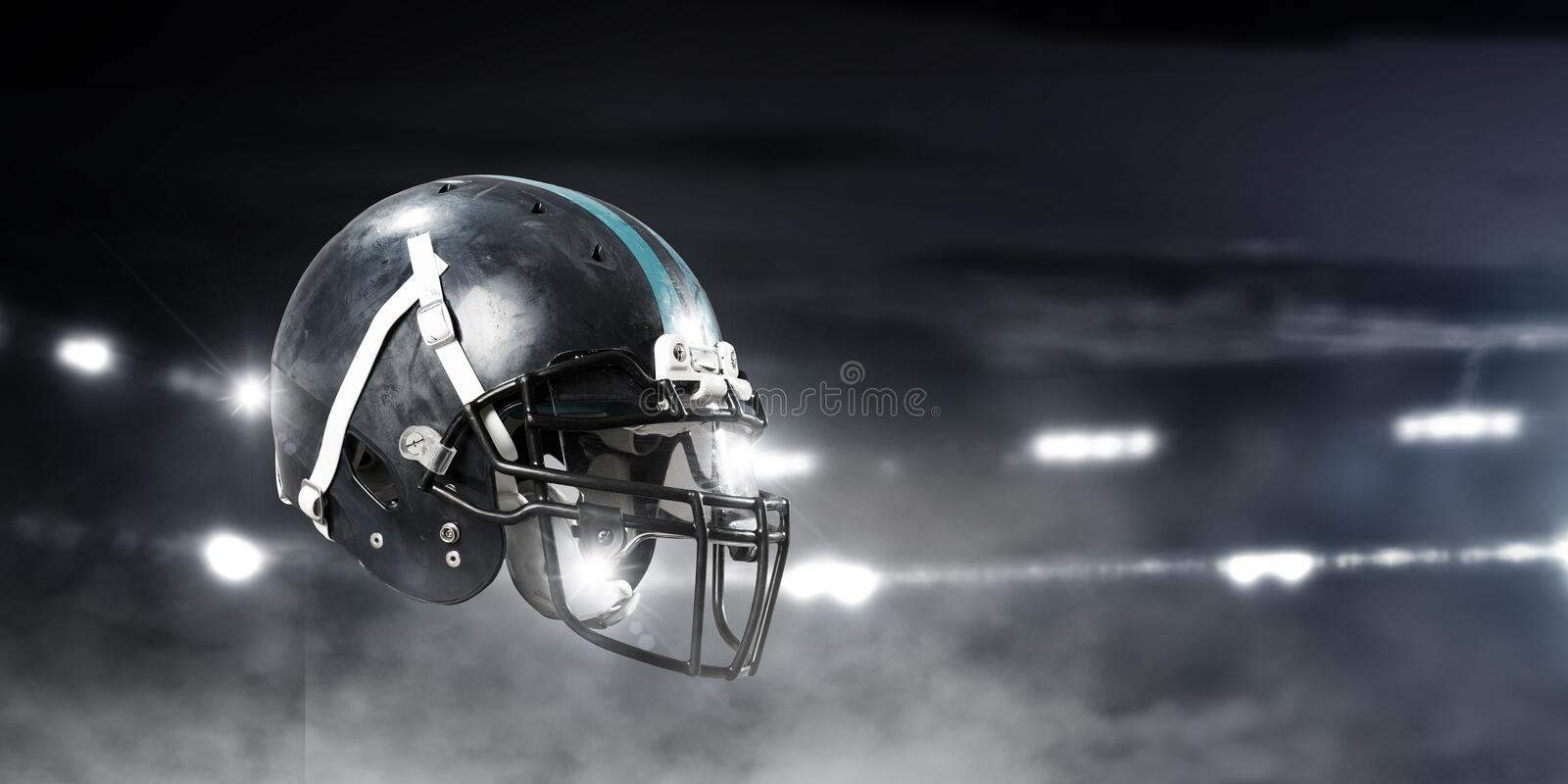 It is game time. Mixed media. American football helmet against rugby stadium. Mixed media stock images
