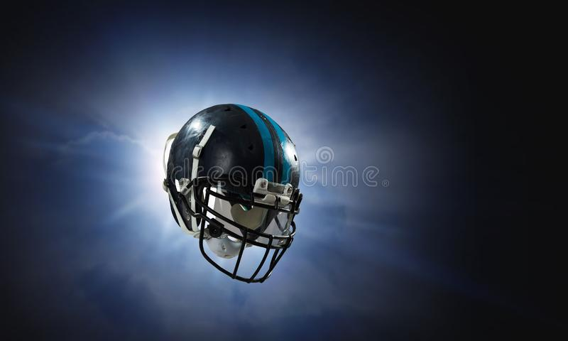 It is game time. Mixed media. American football helmet against rugby stadium. Mixed media royalty free stock photos
