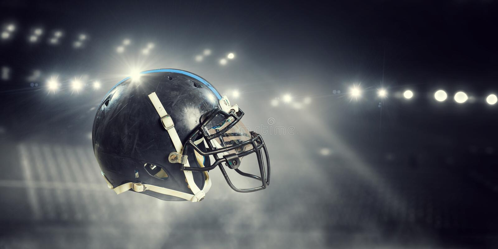 It is game time. Mixed media. American football helmet against rugby stadium. Mixed media stock photo