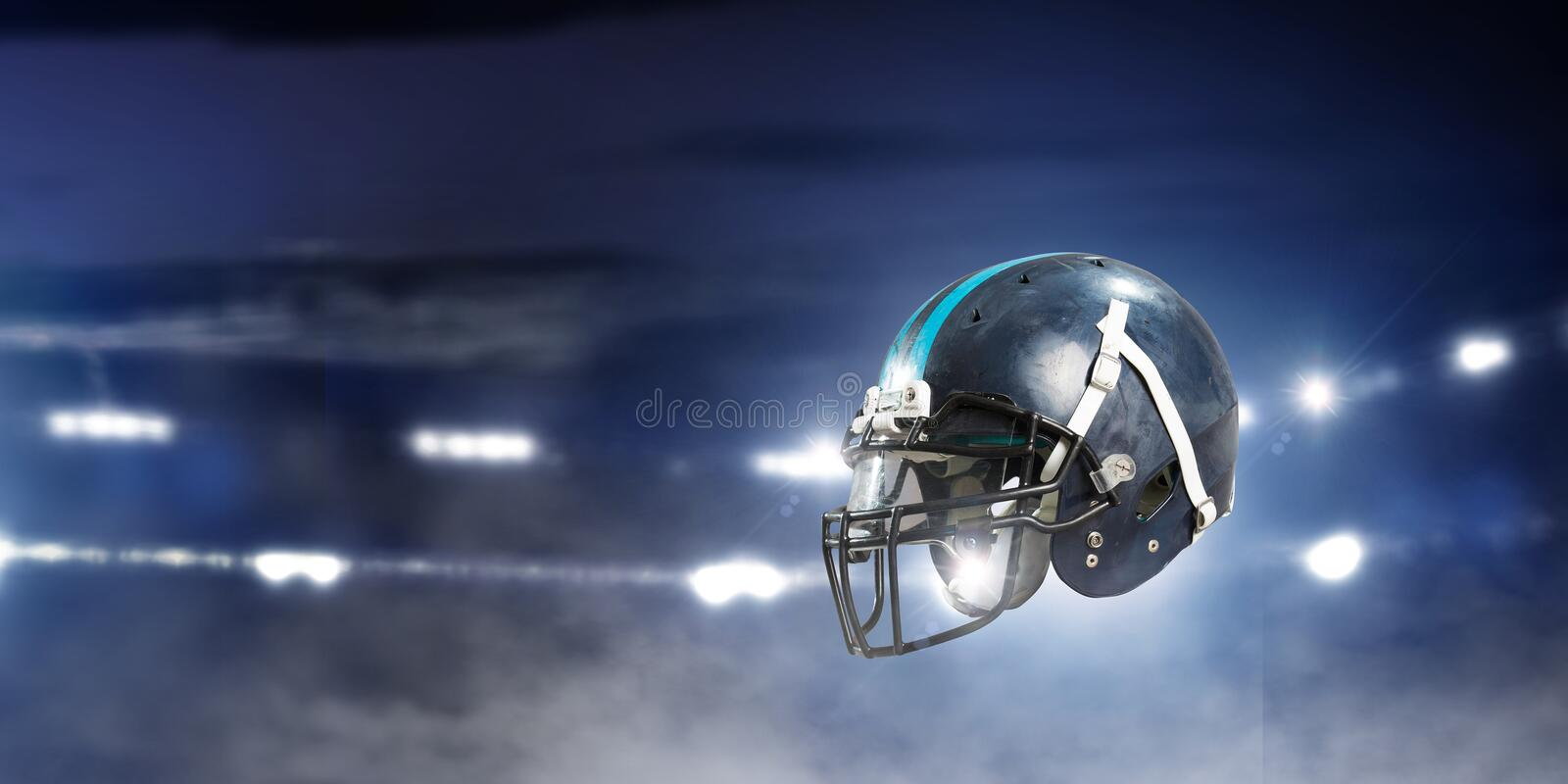 It is game time. Mixed media. American football helmet against rugby stadium. Mixed media stock image