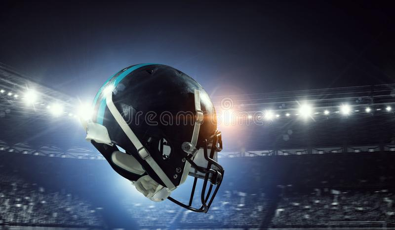 It is game time. Mixed media. American football helmet against rugby stadium. Mixed media royalty free stock image