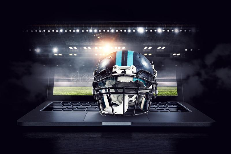 It is game time. Mixed media. American football helmet on laptop against rugby stadium. Mixed media royalty free stock photography