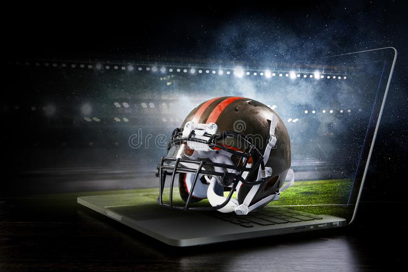 It is game time. Mixed media. American football helmet on laptop against rugby stadium. Mixed media stock images