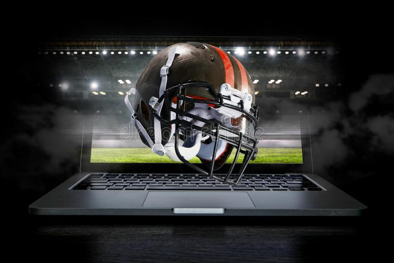 It is game time. Mixed media. American football helmet on laptop against rugby stadium. Mixed media stock image