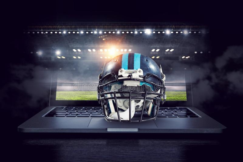 It is game time. Mixed media. American football helmet on laptop against rugby stadium. Mixed media royalty free stock images
