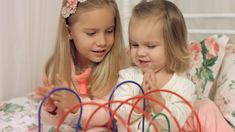 Game of two sisters with interesting educational toy. Game of two sisters with the interesting educational toy stock photos